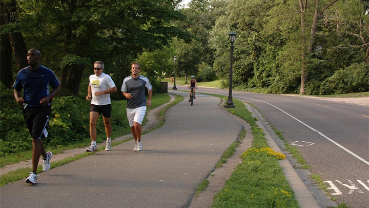 three people run on a paved trail with a cyclist approaching in the background