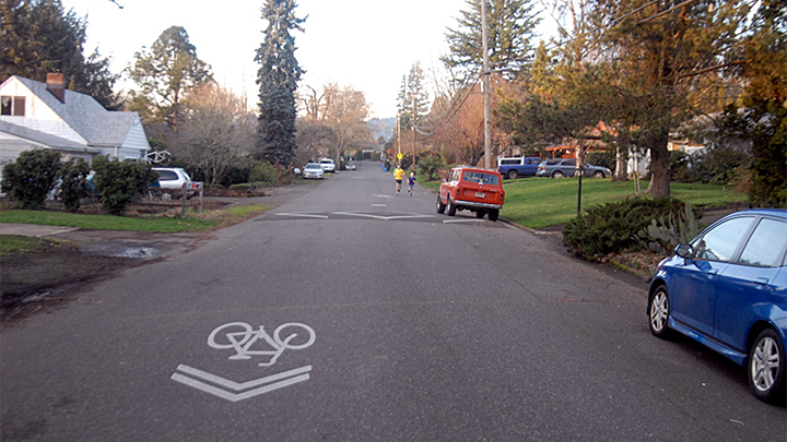 a residential street with cars parked, people jogging, a painted speed bump and a painted bike sharrow