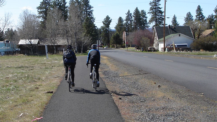 two cyclists ride on a paved path separated from the main roadway