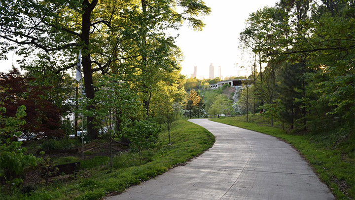 a paved trail meanders through a wooded area with a building in the background
