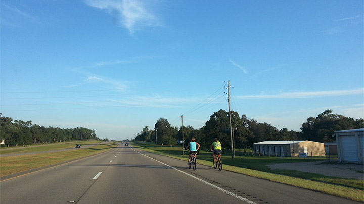 two cyclists ride on a shoulder aside an aterial road