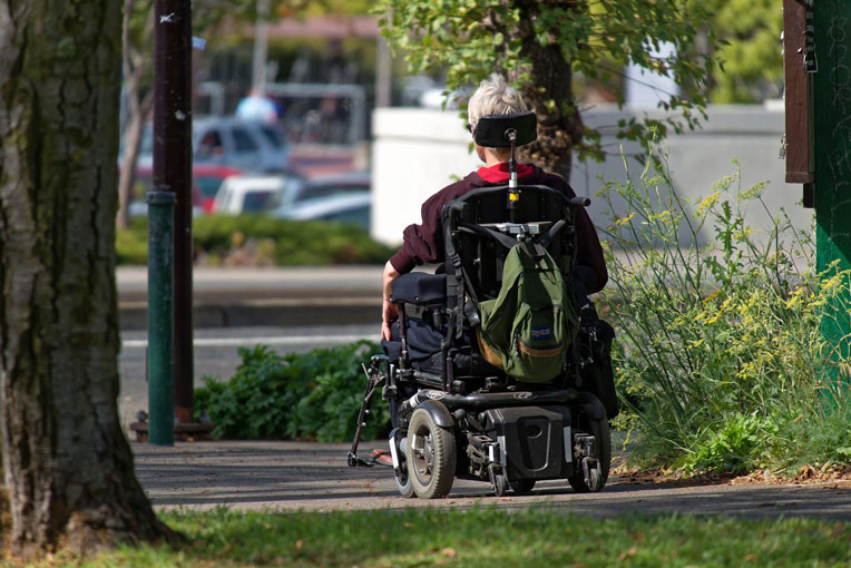 A person in a wheelchair using a sidewalk